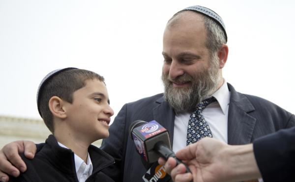 Menachem Zivotofsky stands with his father, Ari Zivotofsky, outside the Supreme Court in Washington in 2014.