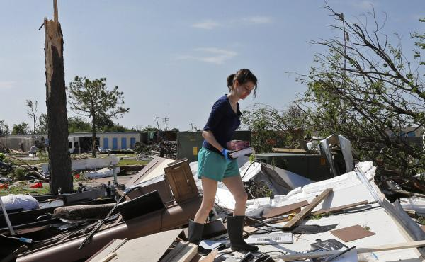 A photo from Thursday shows Dillan Taylor salvaging items from her destroyed recreational vehicle in Oklahoma City following a tornado there. More tornadoes hit the Plains states over the weekend.
