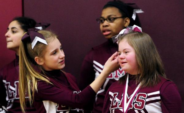 Alyssa Smith readjusts Desiree Andrews' hair as they cheer for the seventh grade basketball team at Lincoln Middle School on Monday in Kenosha, Wis. The gym has been dubbed