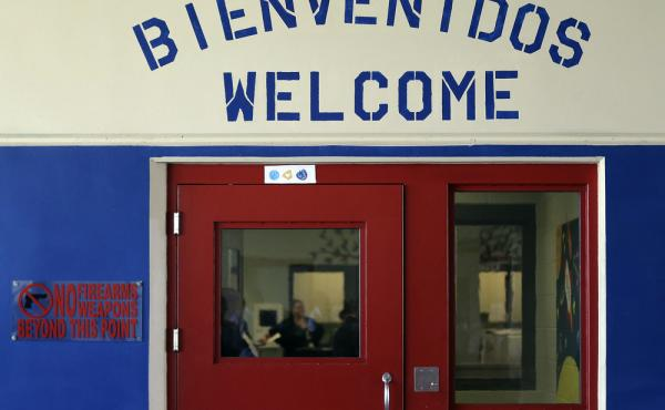 A sign in Spanish and English above the entrance to a secured entrance area at the Karnes County Residential Center in Karnes City, Texas.