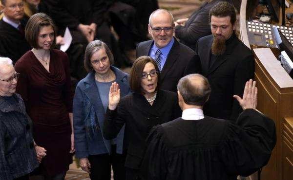 Oregon Secretary of State Kate Brown is sworn in as Oregon Governor by Oregon Chief Justice Thomas A. Balmer in Salem, Ore., on Wednesday.