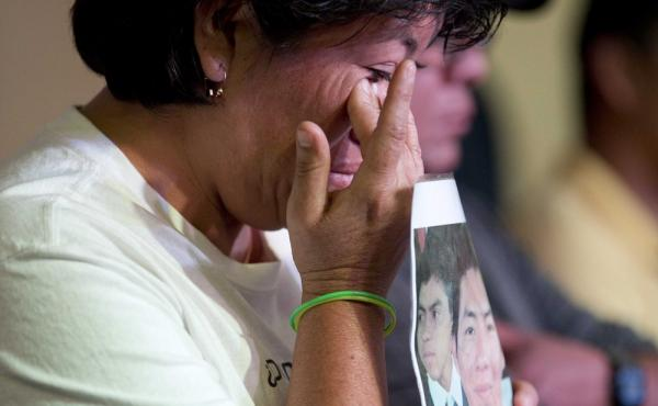A relative holding a picture of one of the missing students, wipes a tear from her face during a press conference in Mexico, City.