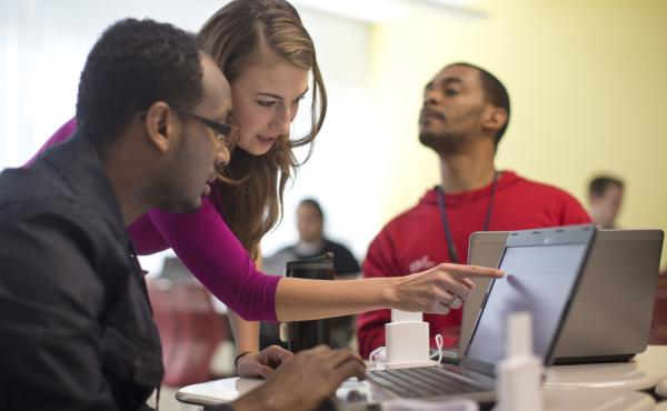 Kaylin Wainwright (center) works with student Natnael Gebremariam (left) during a GED preparation class in Washington, D.C. Seated at right is student Sibusiso Kunene.