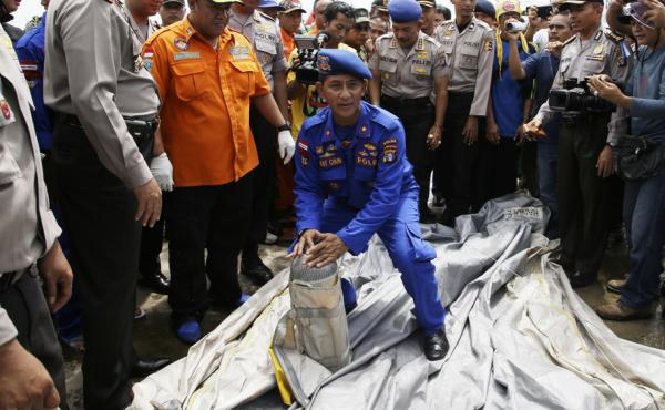 An Indonesian police officer in Kumai port in Pangkalan Bun carries part of a plane found floating on the water near the site where AirAsia Flight 8501 disappeared on Sunday.