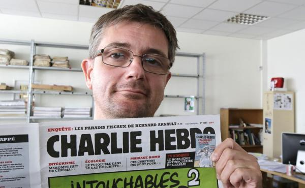 Stephane Charbonnier, the editor of Charlie Hebdo, poses with his magazine on Sept. 19, 2012. The magazine, which was attacked today, is part of a long tradition of French satire.