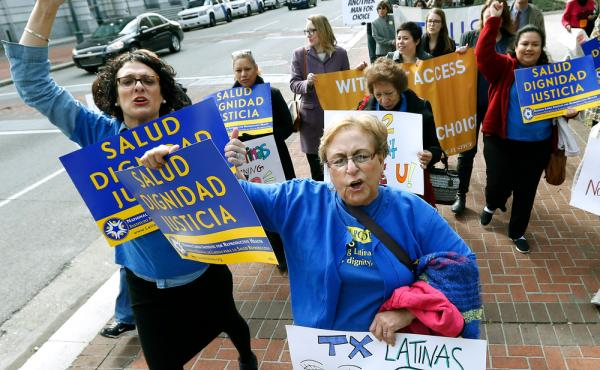 Women with the National Latina Institute for Reproductive Health demonstrate Wednesday outside the 5th U.S. Circuit Court of Appeals in New Orleans. A federal appeals court in New Orleans is considering whether a Texas law puts up an unconstitutional obst
