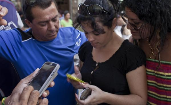 Cubans try to connect to the ETECSA server during a May 9 service outage as they wait with other customers outside the offices of the state telecom monopoly in Havana, Cuba. Cuba's government has blamed technological problems on a U.S. embargo. Critics of