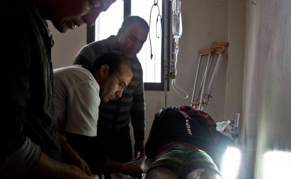 Dr. Mohammed Arif helps treat a wounded patient at a field hospital in Kobani, Syria. Most of the clinics in this besieged Syrian border town are now in ruins. Only one still stands, its location kept secret lest it be targeted.