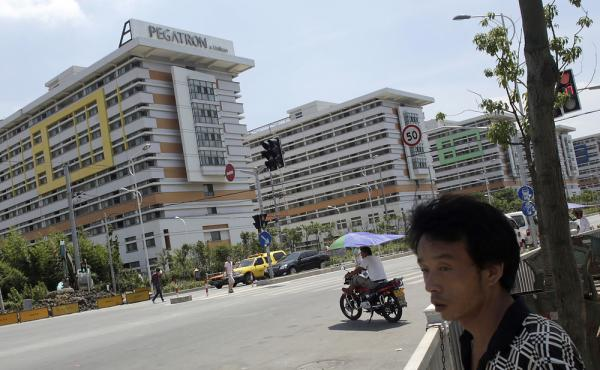 People walk near several buildings of a Pegatron factory in Shanghai, China, in July 2013. Pegatron is a supplier for Apple products.
