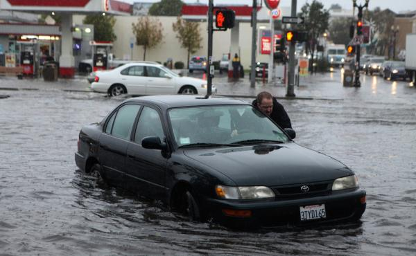Mark Kunze of San Bruno pushes his stalled vehicle out of a flooded intersection Thursday in South San Francisco.