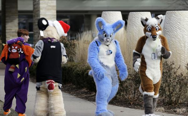 Frederic Cesbron (right) and Maxim Durand walk on the street outside the Hyatt Regency O'Hare hotel in Rosemont, Ill., on Sunday. Thousands of people were evacuated earlier after a chlorine gas leak at the hotel, which is hosting the 2014 Midwest FurFest