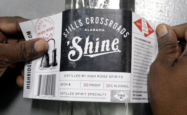 Cynthia Thomas puts labels on bottles of moonshine near Union Springs, Ala., Friday, Oct. 25, 2013. Last year, High Ridge Spirits — Alabama's first legal distillery since Prohibition — joined the growing trend of more than 600 craft distilleries