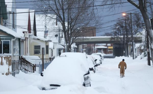 A man walks along a snow-covered street Thursday. Some areas of northern and western New York state could get a combined total of 8 feet of snow this week.