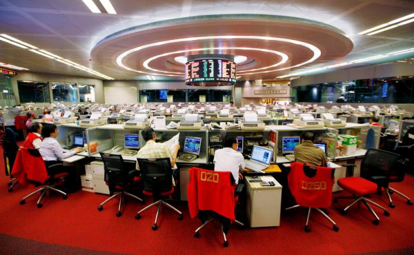Floor traders study stock prices in the Hong Kong Stock Exchange in 2013.
