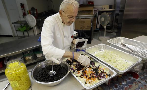 Homeless advocate Arnold Abbott, 90, director of the nonprofit group Love Thy Neighbor Inc., prepares a salad Wednesday in the kitchen of The Sanctuary Church in Fort Lauderdale, Fla. Abbott was recently arrested, along with two pastors, for feeding the h