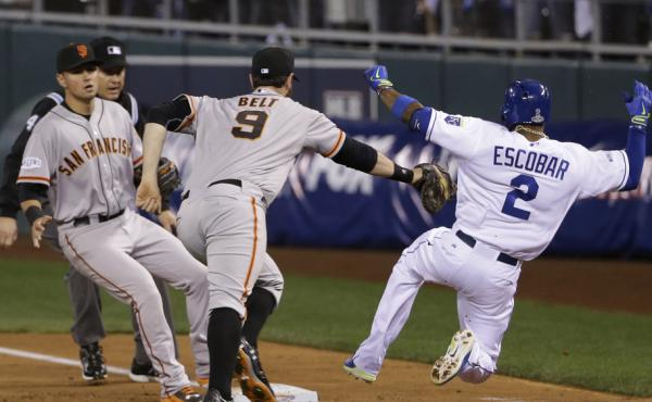 The San Francisco Giants' Brandon Belt can't reach the Kansas City Royals' Alcides Escobar as he slides safely to first base on an infield single Tuesday night during the second inning of Game 6 of baseball's World Series in Kansas City, Mo. Escobar event