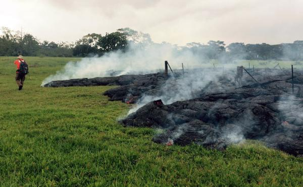 A geologist maps the margin of the lava flow in the open field below Cemetery Road near the town of Pahoa on the Big Island of Hawaii. Dozens of residents from the village may be forced to evacuate.