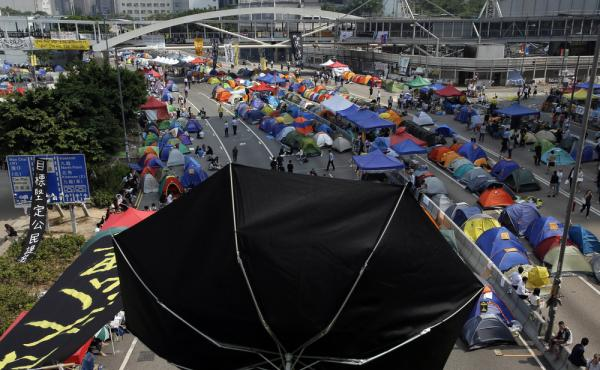 An umbrellas is placed near tents set up by pro-democracy protesters in an occupied area near government headquarters in Hong Kong on Thursday. Hong Kong officials have revived an offer for talks with the activists, but also emphasized that Beijing will n