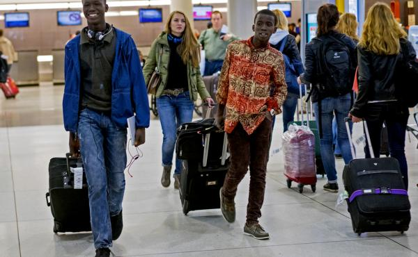 Thomas Nellon (left), 17, and his brother Johnson Nellon, 14, of Liberia smile at their mother in the arrivals area at John F. Kennedy International Airport in New York earlier this month. The brothers received a health screening upon arrival. The U.S. sa