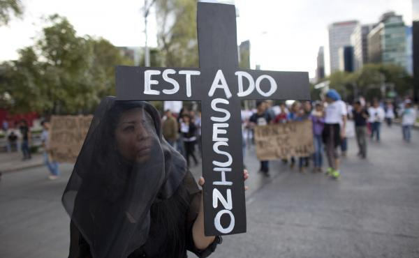 "A woman wears a black veil and carries a cross reading in Spanish ""Assassin State,"" as thousands march down one of the capital's main boulevards to demand that the government find the 43 students who disappeared in southern Guerrero State."