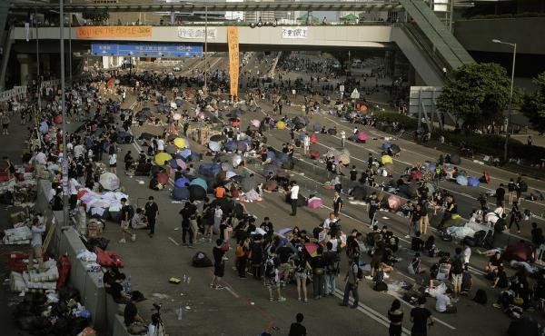 Pro-democracy activists sleep, rest and walk on a street near the government headquarters Tuesday in Hong Kong. Students and activists, many of whom have been camped out since late Friday, spent a peaceful night singing as they blocked streets in Hong Kon
