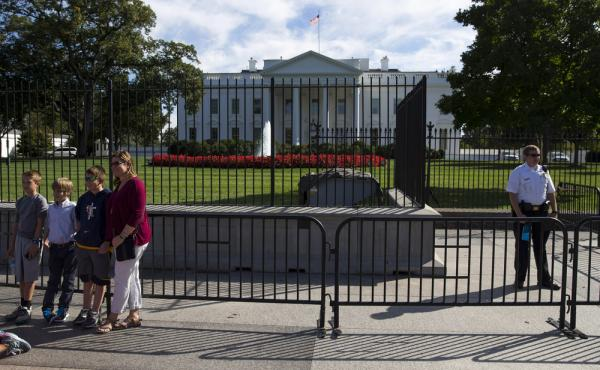 A Secret Service police officer stands nears tourists outside the White House on Monday.
