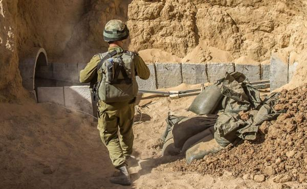 An Israeli army officer walks near the entrance of a tunnel allegedly used by Palestinian militants for cross-border attacks, at the Israel-Gaza border. A network of tunnels Palestinian militants have dug from Gaza to Israel is taking center stage in the