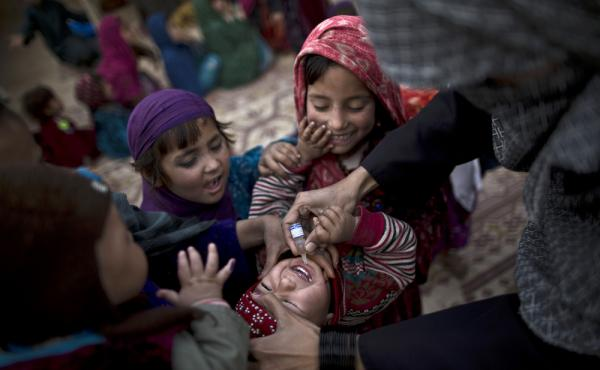 On the outskirts of Islamabad, a Pakistani health worker vaccinates an Afghan refugee against polio.
