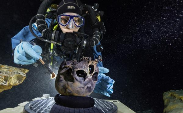 In this June 2013 photo provided by National Geographic, diver Susan Bird, working at the bottom of Hoyo Negro, a large dome-shaped underwater cave in Mexico's Yucatan Peninsula, brushes the Naia skull found at the site.