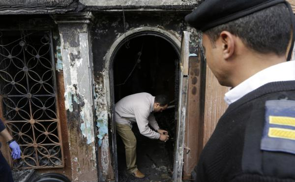 An Egyptian forensic expert checks the gate of the nightclub that was attacked in Cairo Friday. At least 16 people were killed in the attack.