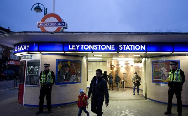 British police officers stand outside Leytonstone underground train station in east London on Monday. Police are stepping up patrols at transport hubs after Saturday's stabbing attacks, which injured three.