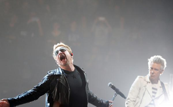 Bono (left) and Adam Clayton of U2 perform on stage during a concert, in Paris on Sunday. On Monday, U2 had Eagles of Death Metal join them onstage.