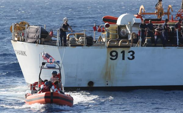 A U.S. Coast Guard crew (foreground) with six Cubans who were picked up in the Florida Straits in May. A larger Coast Guard vessel is in the background. The number of Cubans trying to reach the U.S. has soared in the past year. Many Cubans believe it will