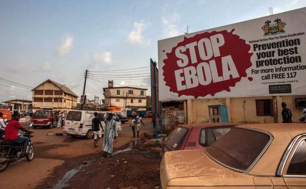A corpse has tested positive for the Ebola virus in Sierra Leone, a day after world health officials declared West Africa free of the disease. On Friday, people pass a banner reading