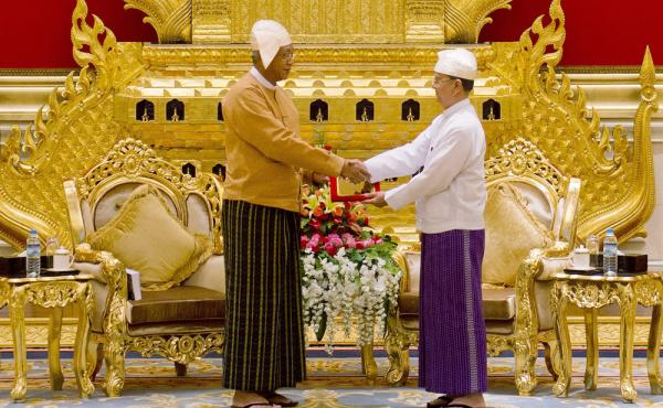 Myanmar's new president U Htin Kyaw (left), receives the presidential seal from outgoing president U Thein Sein during a handover ceremony at the presidential palace in Naypyidaw on Wednesday. The military ruled Myanmar, directly or indirectly, for more t
