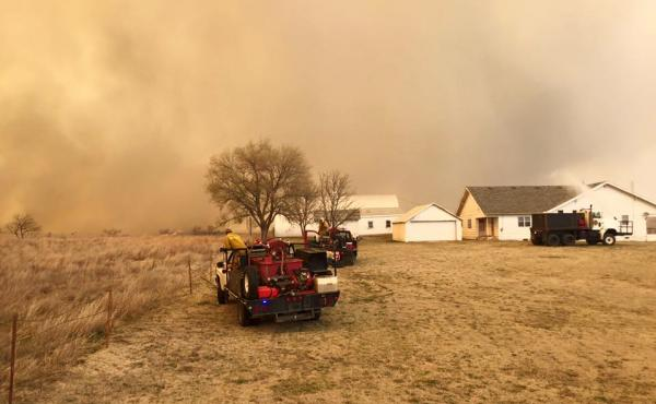 Volunteer firefighters from the Dewey County Task Force work a blaze southwest from Freedom, Okla., on Tuesday.