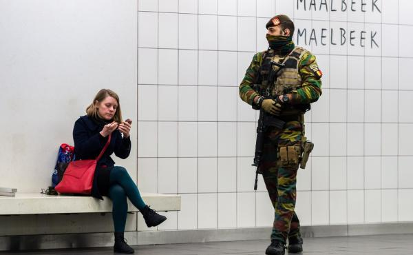 A woman waits for her train Monday at the Maelbeek metro station in Brussels, as a soldier patrols the platform. The station, where more than a dozen people died in an attack on March 22, reopened Monday.