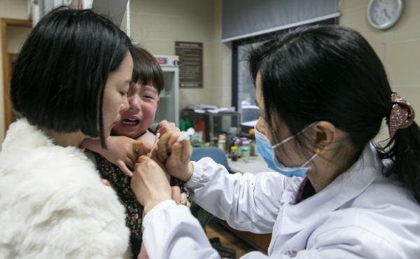 A woman holds her child to receive rabies vaccines at Hangzhou Hospital for the Prevention and Treatment of Occupational Disease as the child got scratched by a cat on March 22, 2016 in Hangzhou, Zhejiang Province of China. A case of illegal vaccines that
