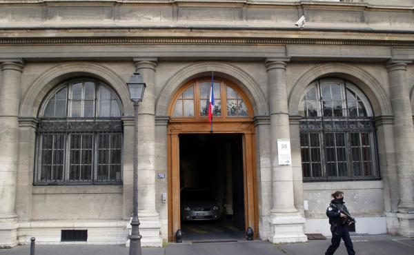 A police officer guards the entrance of the judicial police headquarters in Paris. The French prosecutor's office said Salah Abdeslam, the key suspect in the Paris attacks, was transferred from Belgium to France on Wednesday morning.
