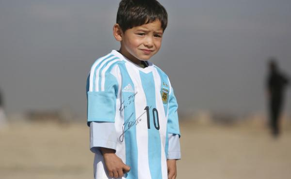 Five-year-old Murtaza Ahmadi, an avid Lionel Messi fan from Afghanistan, poses in a signed jersey from the Argentinian soccer great on Feb. 26. The boy's father says the media coverage led to threats toward the family.