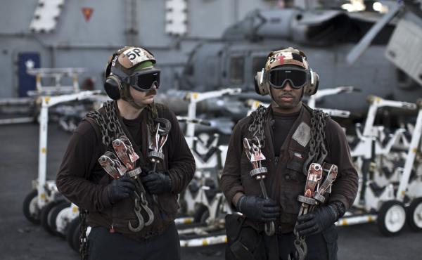 U.S. Navy air wing captains pause on the flight deck of the aircraft carrier USS Theodore Roosevelt last September. Every day, the steam-powered catapult aboard this massive ship flings American fighter jets into the sky, on missions to target the extremi