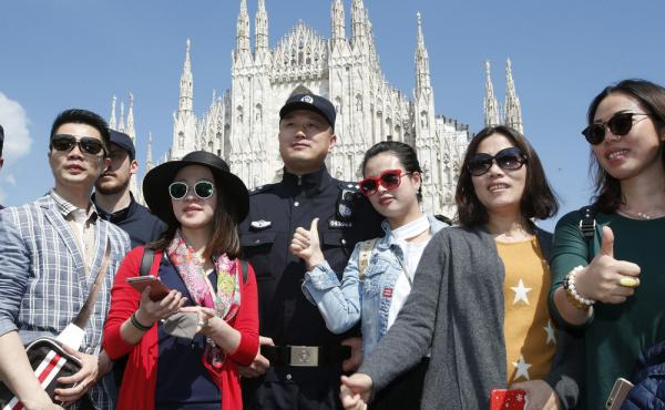 A Chinese police officer poses with Chinese tourists in front of Milan's cathedral on May 3. Chinese policemen are on patrol with Italian officers to help make Chinese visitors feel safer.