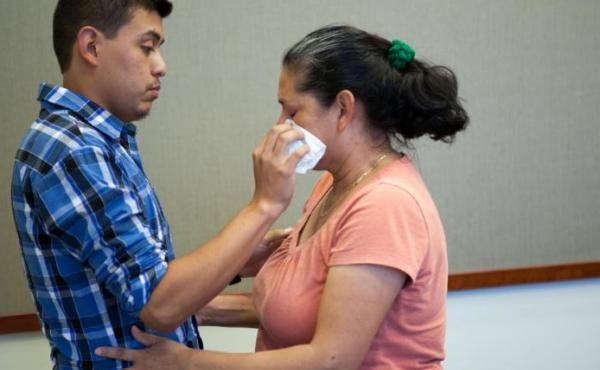 Steven Hernandez wipes a tear from his mother's eye after seeing her for the first time in 20 years in San Bernardino, Calif., on Thursday. Hernandez, 22, was abducted by his father in 1995 when he was 18 months old. Since that time, Maria Mancia, 42, had