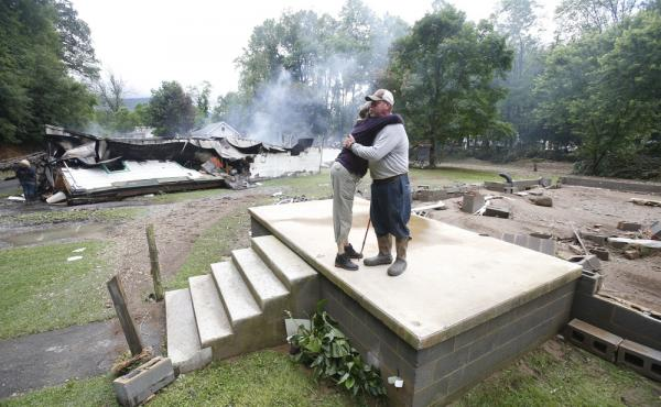 Jimmy Scott gets a hug from Anna May Watson (left) as they clean up from severe flooding in White Sulphur Springs, W. Va., on Friday.