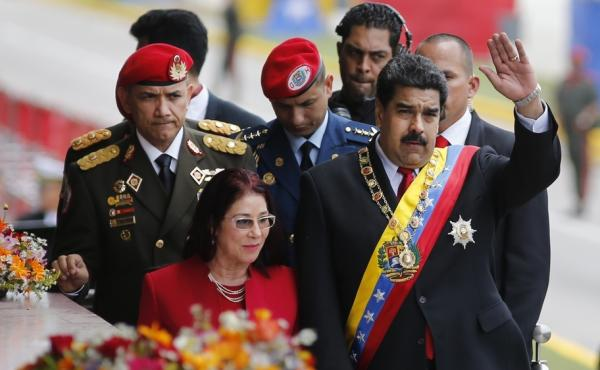 Venezuela's President Nicolas Maduro waves to supporters as he walks with his wife Cilia Flores in the capital Caracas on July 5, Venezuela's Independence Day. As the country's crisis has deepened, Maduro has lost support, but the military remains on his