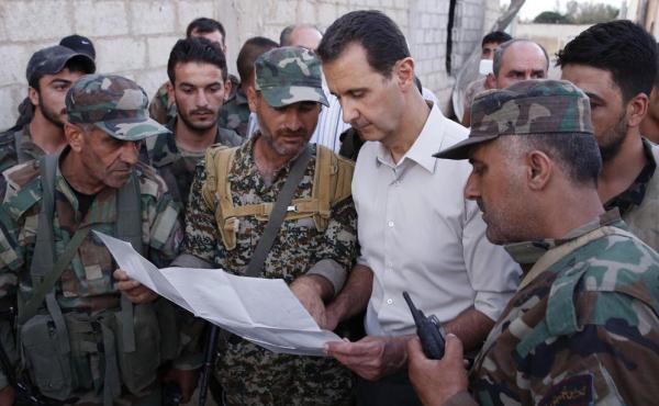 Syrian President Bashar Assad (white shirt) speaks with Syrian troops in the suburbs of Damascus on June 26, in a photo released by the official SANA news agency. The U.S. and Russia are working on proposal to coordinate their bombing campaigns in Syria,