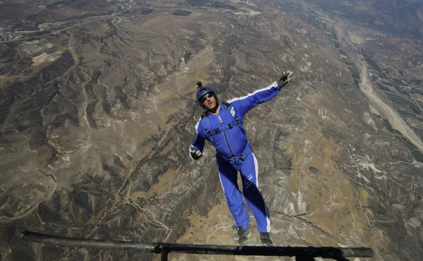 Luke Aikins jumps from a helicopter during his training on Monday, in Simi Valley, Calif. After more than 25 years of skydiving, Aikins ditched his chute to free fall 25,000 feet above the desert terrain.