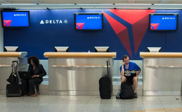 Passengers wait at Hartsfield-Jackson Atlanta International Airport after a computer systems failure on Monday caused Delta to delay or cancel hundreds of flights.