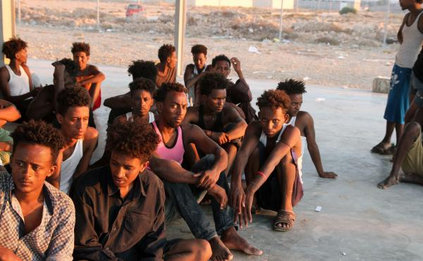 Rescued migrants sit on the coast of Khoms, some 100 kilometres (60 miles) from the Libyan capital Tripoli, on July 26, 2019. About 145 migrants were rescued by the Libyan coastguard, and survivors had reported that about 150 people remained missing.