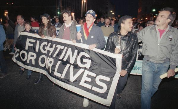 Marchers at a candlelight vigil in San Francisco, Calif., carry a banner to call attention to the continuing battle against AIDS on May 29, 1989. The city was home to the nation's first AIDS special care unit. The unit, which opened in 1983, is the subjec